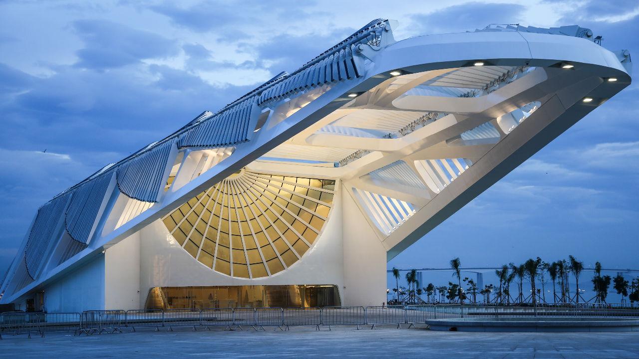 Fachada do Museu do Amanhã de longe toda branca com as luzes de dentro acesas e entardecer / Foto: Bernard Lessa