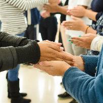 Imagem com foco no cumprimento de mãos entre voluntários e colaboradores do Museu do Amanhã / Foto: Laura Lima