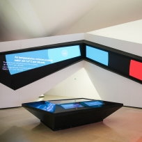 Área Amanhãs da Exposição Principal, com paredes em formato origami, coberta por telas em ângulos e, ao centro, uma mesa interativa