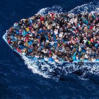 Foto aérea que mostra barco superlotado de refugiados atravessando o mar