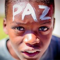 Foto de menino negro com a palavra paz escrita com tinta branca em sua testa