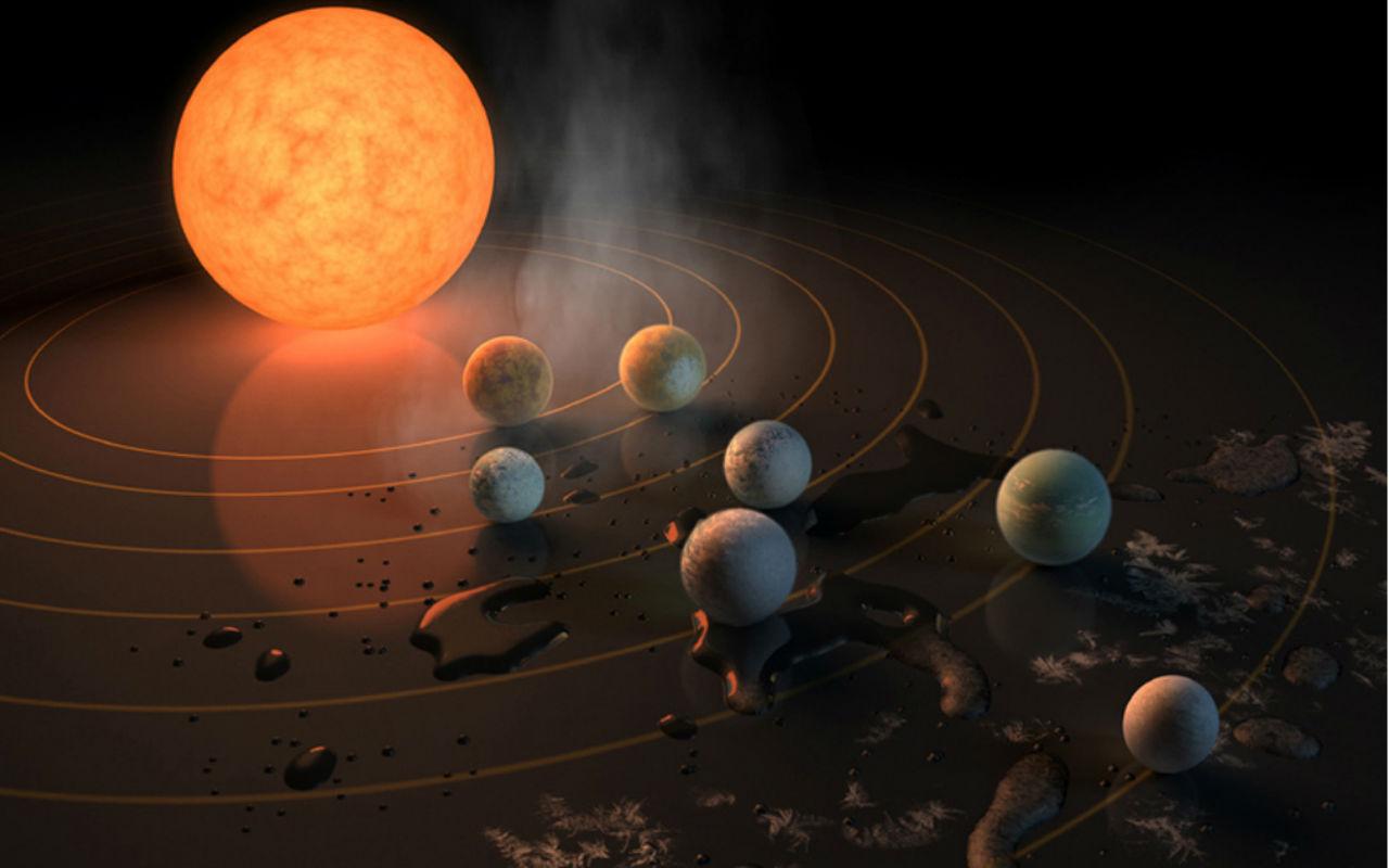 Ilustração: a estrela anã (laranja e grande) TRAPPIST-1 e sete planetas menores na cor cinza em sua órbita / Foto: NASA / JPL-Caltech