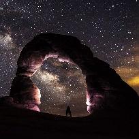 Imagem do céu a noite com estrelas brilhando e uma pessoa embaixo de um arco admirando  / Foto: Pixabay