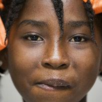 Criança negra sorrindo de frente para a câmera com laços laranjas no cabelo / Foto: UN Photo/Marco Dormino CC BY-NC-ND 2.0