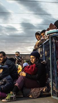 Pessoas em situação de refúgio sentadas e agasalhadas e uma multidão atrás de uma cerca