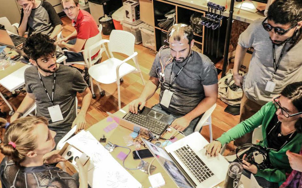 Pessoas ao redor da mesa mexendo no computador no Laboratório de atividades