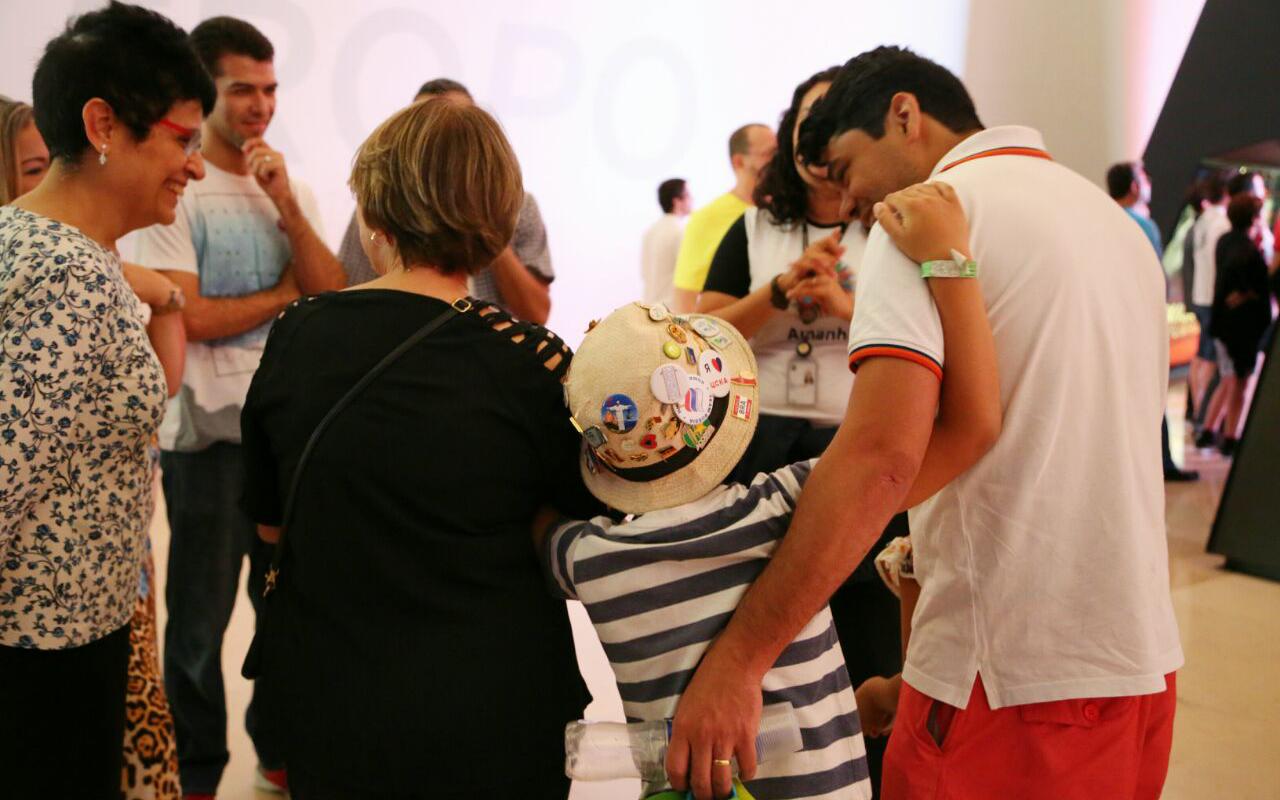 Grupo de visitantes do Museu com homens, mulheres e crianças sorrindo durante uma visita