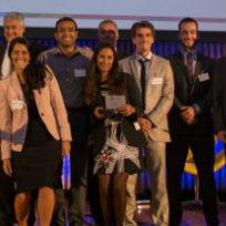 Equipe da empresa ENGIE em cima do palco e com telão de fundo com a identidade visual do evento Prêmio de Inovação ENGIE