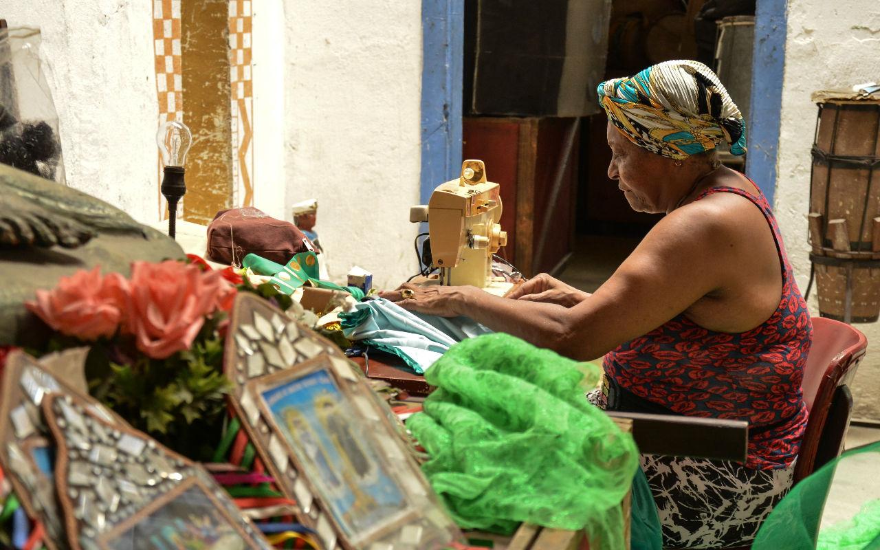 moça sentada costurando roupa na região portuária