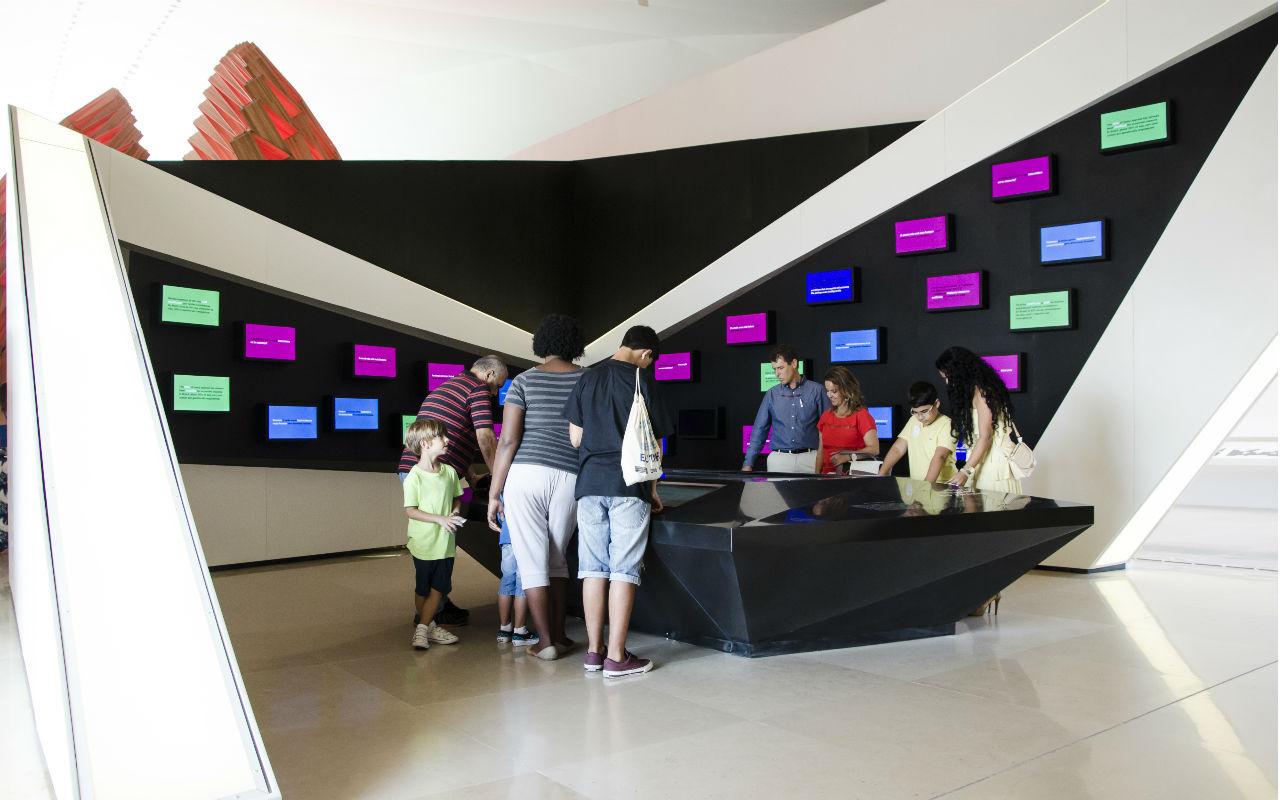Pessoas usando as telas interativas do Museu do Amanhã / Foto: Byron Prujansky