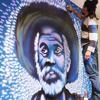 Caio Chacal, artista e produtor do Laboratório de atividades do Amanhã em cima de um banco grafitando na parede da exposição Rolé pelo Rio hackeado no Museu do Amanhã. / Foto: LAA