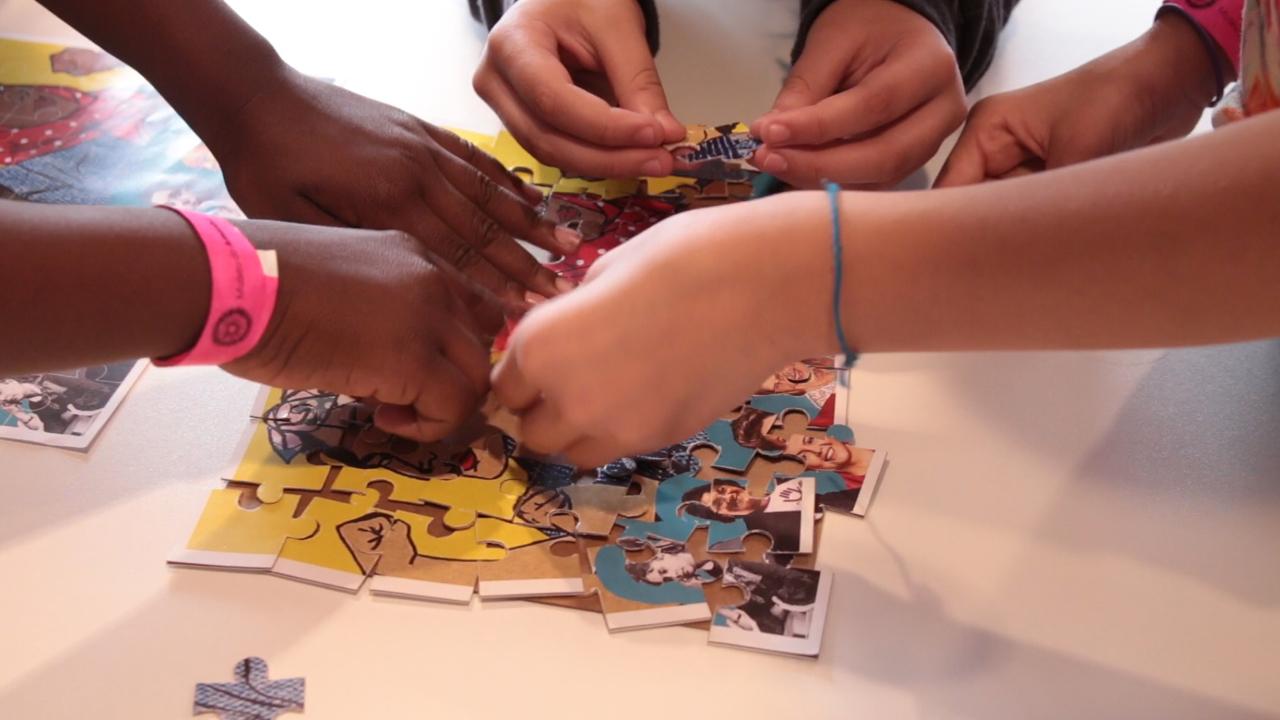Mãos de crianças montando um quebra cabeça