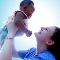 Mulher branca levantando uma criança negra e olhando com ternura para ela