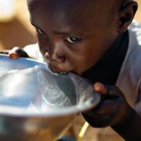 Criança negra bebendo água em uma tigela prata / Foto: United Nations Photo