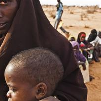 Mulher segurando criança pequena no colo e um grupo de pessoas sentadas atrás