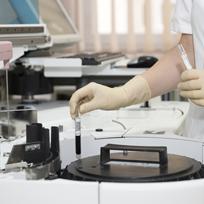 Mãos com luvas médicas manipulando tubo de ensaio