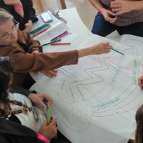 Grupo de pessoas sentadas desenhando juntas