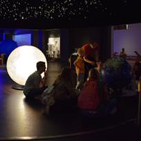 Grupo de pessoas realizando uma visita ao Science Museum, sentadas enquanto uma pessoa aponta para um globo