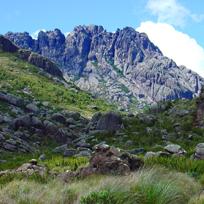 Área com grama e pedras e ao fundo uma elevação rochosa