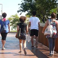 Quatro pessoas de costas caminhando em área aberta com piso de madeira e árvores ao fundo