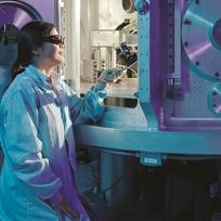 Mulher cientista observando com óculo um equipamento grande de ciência / Foto: Pixabay
