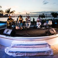 Foto feita na lateral do museu, com banda de música tocando em palco circular branco e, ao fundo, a Baía de Guanabara no pôr do sol.