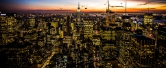 Foto panorâmica de cidade ao anoitecer com muitos prédios iluminados