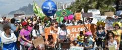 Homens e Mulheres na rua, alguns de bicicleta, segurando cartazes no ato da Marcha Mundial pelo Clima