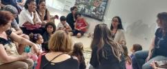 Crianças e adutos sentados em roda  no terreiro de atividades do Museu do Amanhã