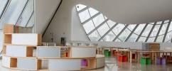 Foto do terreiro das curiosidades no Museu do Amanhã. Espaço vazio todo branco com cadeiras e mesas baixas coloridas.  | Foto: Bernard Lessa