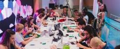 Mulheres sentadas em volta de uma mesa branca concentradas aplicando novas tecnologias vestíveis /  Foto: Renan Lima