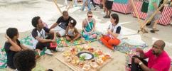 Crianças e adultos em uma roda de conversa na área externa do Museu sentados em almofadas coloridas / Foto: Thales Leite