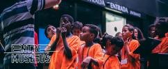Foto de um grupo de crianças participantes do Entre Museus com a blusa laranja do projeto prestendo atenção no que o professor, que está de costas para a câmara, está dizendo. Por cima da foto, no canto inferior esquerdo, o logo do projeto.