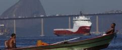 Dois homens em um pequeno barco na Baía de Guanabara com o Pão de Açúcar ao fundo