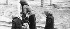 Senhora de costas andando de mãos dadas com duas crianças e uma terceira criança andando atrás delas