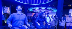 Duas pessoas na área de colaboração da exposição Inovanças, andando de bicicleta para fazerem um lustre com luz azul acender